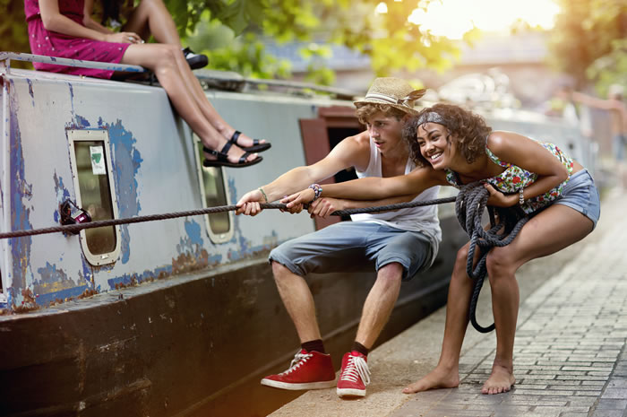 Two young people pulling on canal boat rope